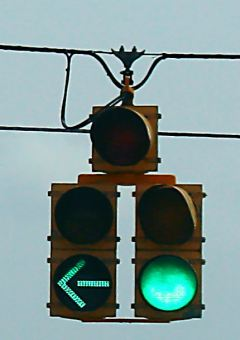 dual-yellow-traffic-signal-hanging-on-wire-showing-left-turn-arrow-and-green-light